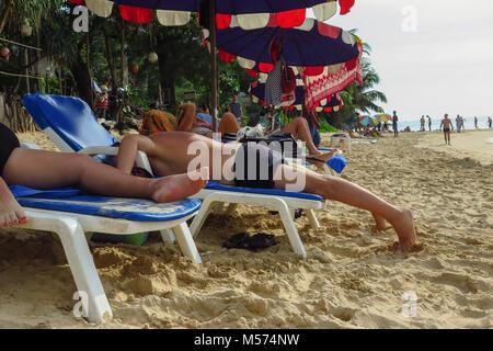 Funny shot of caucasian middle aged man lying face vers le bas sur une chaise longue en train de bronzer sur une plage, pas de visage