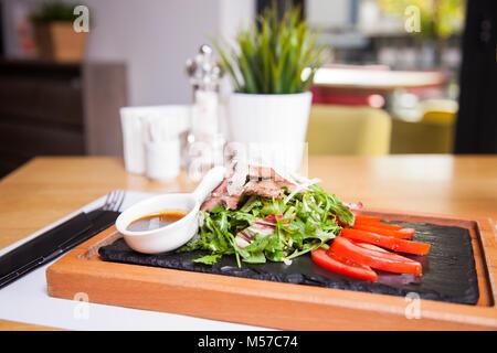 Le steak grillé ou frit à la perfection. Pavé de boeuf en tranches , servi avec des feuilles de salade verte et Banque D'Images
