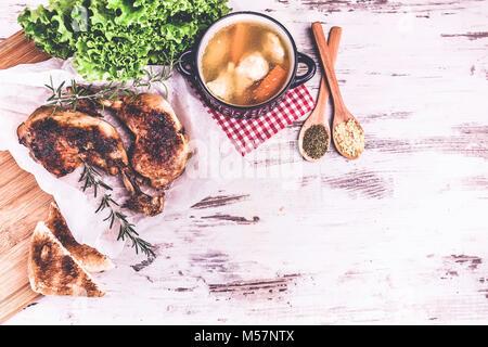 Délicieux pilons de poulet rôti au romarin et d'épices dans des cuillères et de la soupe au poulet servi dans un Banque D'Images