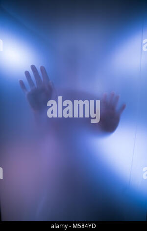Silhouette of Woman's hands derrière Verre bleu Banque D'Images