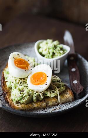 La purée d'avocat, œuf et fromage sur du pain grillé. Mode de vie sain, concept de saine alimentation. Photo alimentaire Banque D'Images