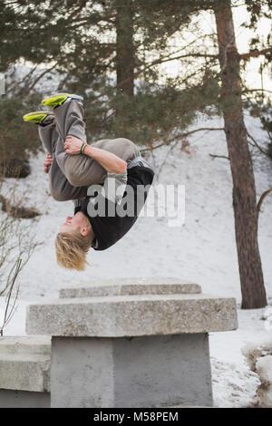 Cheveux blonds adolescent man training parkour saut dans le parc couvert de neige Banque D'Images
