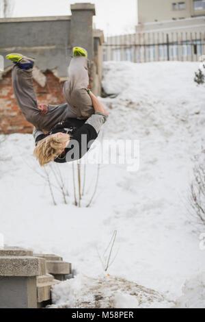 Cheveux blonds adolescent parkour formation guy jump flip dans le parc couvert de neige Banque D'Images