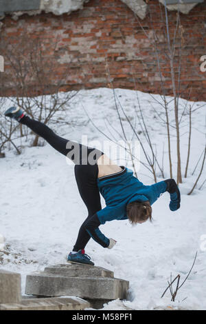 Teen girl jumping flip dans snow winter park - concept parkour free-run Banque D'Images