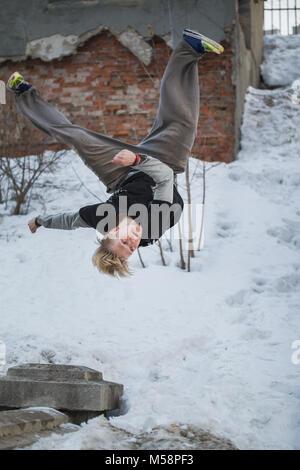Parkour Backflip en hiver snow park - adolescent aux cheveux blonds Banque D'Images