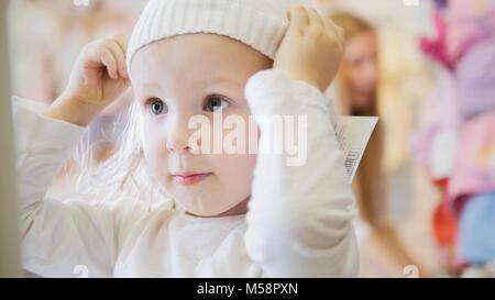 Petite fille essayant des chapeaux blanc Banque D'Images
