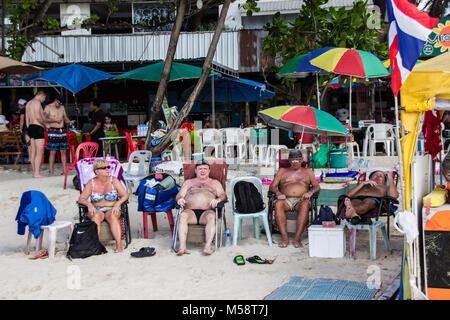 Mâles et femelles matures de touristes européens bronzer / se prélasser sur la plage de Patong, Phuket