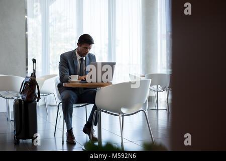 Businessman sitting in airport zone d'attente et de travail sur ordinateur portable. Salon d'attente à l'aéroport Banque D'Images