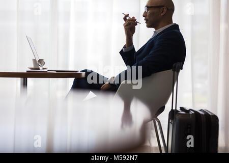 Businessman speaking sur téléphone mobile tout en étant assis à table dans la salle d'attente à l'aéroport. Homme Banque D'Images