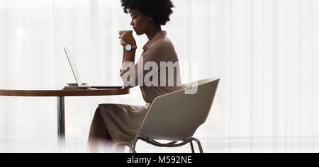 African businesswoman drinking coffee and looking at laptop sur table. Vue latérale du coffre à l'aide de la direction Banque D'Images
