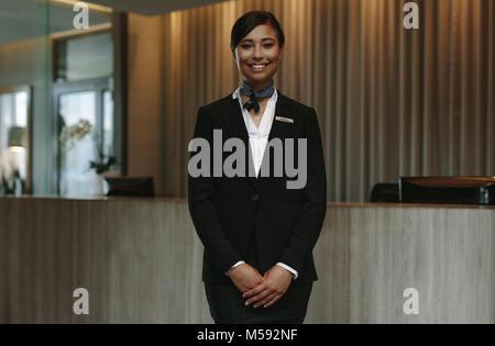 Happy smiling female réceptionniste dans l'hôtel. Concierge belle en uniforme en attente d'accueil des invités. Banque D'Images