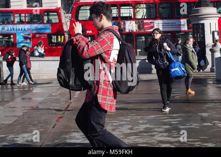 Un jeune homme en prenant une photo avec un smartphone avec un sac à dos sur le dos et le poignet portant une chemise Banque D'Images