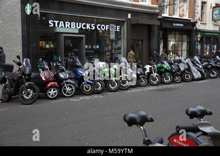 London,UK,21 Février 2018,un roe de motos garées à l'extérieur de l'entreprise Starbucks coffee shop sur un ciel Banque D'Images