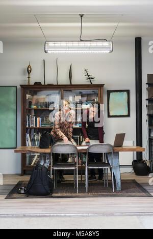 Deux femmes se sont réunis autour de la table dans la zone des bureaux d'un métal, à la technique de l'atelier au Banque D'Images