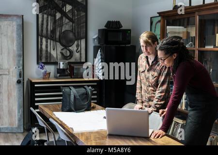 Deux femmes se sont réunis autour de la table dans la zone des bureaux d'un atelier métal, looking at laptop. Banque D'Images