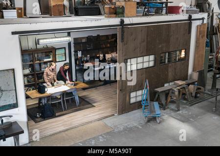 Portrait de deux femmes réunies autour de la table dans la zone de bureaux d'atelier. Banque D'Images