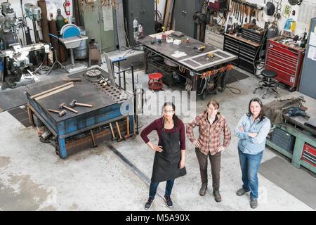 Portrait de trois femmes debout dans l'atelier de métal, looking at camera. Banque D'Images