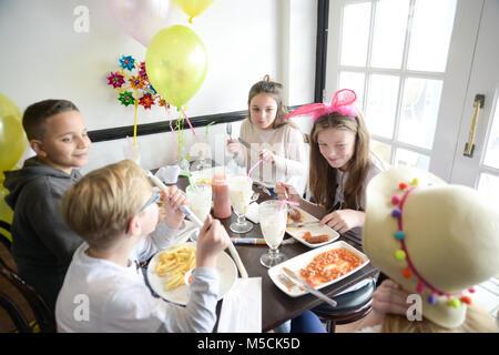 Cinq jeunes enfants sont assis à une table en train de manger les aliments frits parti et de boire des milkshakes Banque D'Images