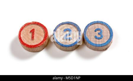 Numéros un et deux sur trois petites pièces en forme de cylindre en bois sur fond blanc Banque D'Images
