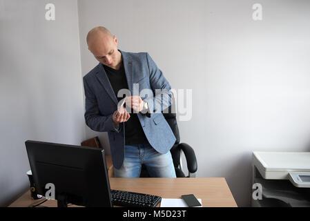 Un jeune homme travaillant dans un bureau avec un ordinateur et un téléphone cellulaire, un portrait pris dans la Banque D'Images