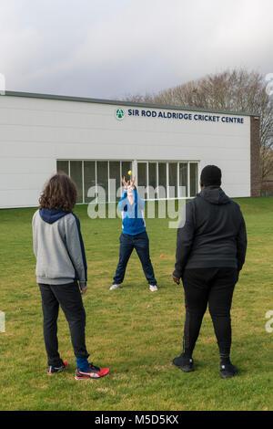 Les étudiants pratiquent à jouer au cricket sur un terrain de jeu de l'école dans le cadre d'une leçon de jeux avec Banque D'Images