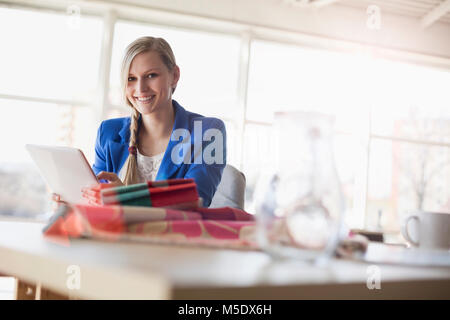 Portrait of young businesswoman using digital tablet in creative office