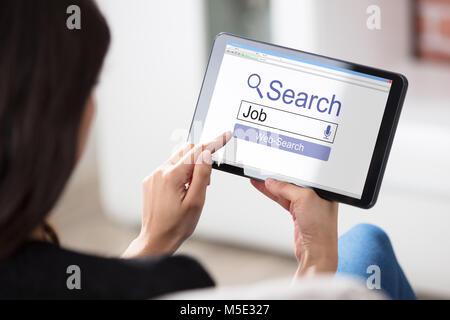 Portrait d'une femme à la recherche d'emploi en ligne sur tablette numérique