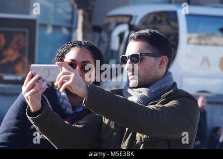Un jeune couple de prendre un avec un smartphone selfies portant des lunettes de soleil en hiver à Trafalgar Square, Banque D'Images