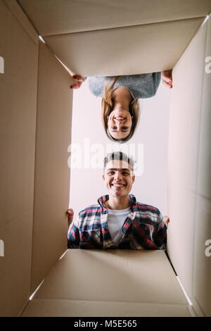 Smiling young couple ouverture d'une boîte en carton et à l'intérieur, Banque D'Images