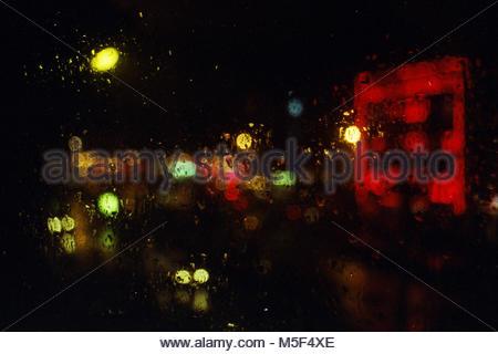 Vue floue de derrière un verre d'un bar sur jour de pluie à Paris Banque D'Images