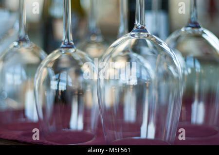 Gros plan du propre, verres vides à l'envers sur un tissu de couleur bourgogne Banque D'Images