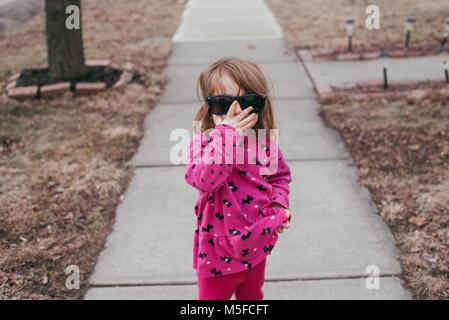 Un bébé fille portant un chandail rose et lunettes, debout sur un trottoir sur une journée chaude et ensoleillée. Banque D'Images