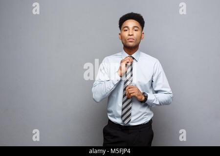 Concept d'affaires - african american businessman professionnel confiant sa cravate cravate sur fond gris Banque D'Images
