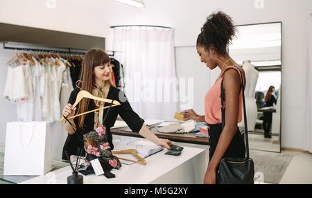 Concepteur commercial client porter lors d'une boutique de mode. Le paiement du client à l'aide d'une carte de crédit. Banque D'Images