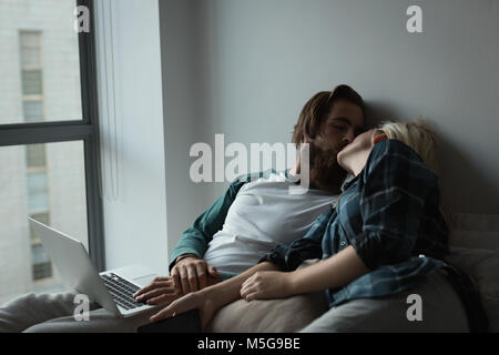 Couple relaxing while using laptop at home Banque D'Images