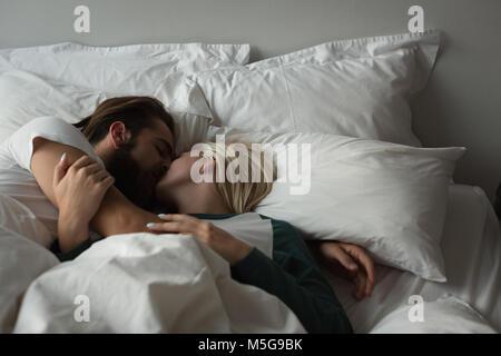 Couple qui s'embrassent dans la chambre Banque D'Images