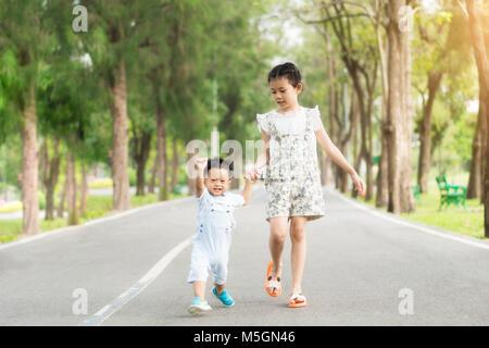 Sœur asiatique tenir la main avec de petits enfants de marcher sur la route en parc avec des rayons de soleil. Banque D'Images