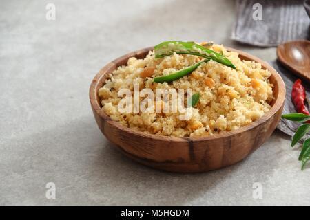Rava Upma - petit-déjeuner de l'Inde du sud avec la semoule servi dans un bol en bois Banque D'Images