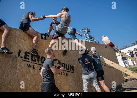 Les participants du défi physique d'aider les uns les autres à surmonter l'obstacle de tall fence Banque D'Images