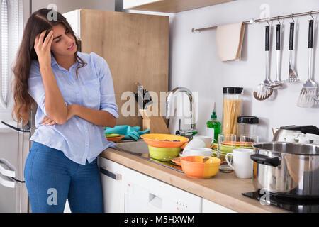 Assez Jeune femme debout près de l'évier de cuisine à la recherche d'ustensiles de cuisine en Banque D'Images