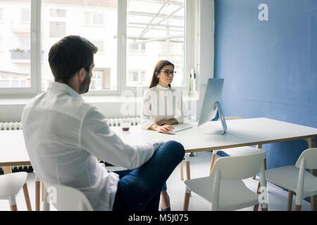 L'homme assis en face de woman using computer in office