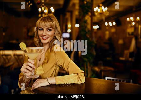 Portrait de femme élégante avec un cocktail dans un bar Banque D'Images