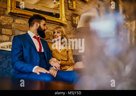 Elegant couple sitting on couch talking