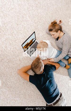 À l'aide de la famille de l'ordinateur portable sur le tapis Banque D'Images
