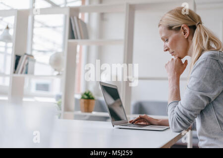Woman using laptop at desk in office