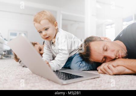 Les parents dormir avec petite fille à l'aide de l'ordinateur portable sur le plancher Banque D'Images