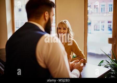 Elegant woman smiling at man in a bar Banque D'Images