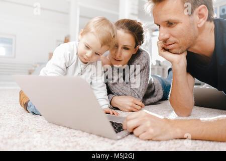 Ordinateur portable à l'aide de la famille à l'étage Banque D'Images
