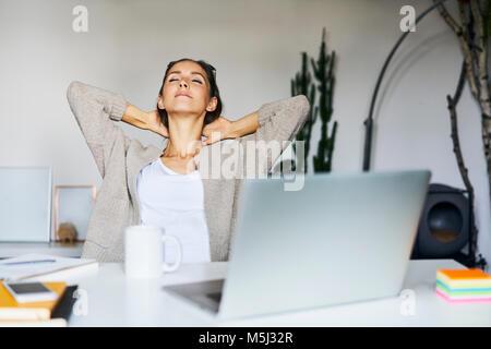 Jeune femme à la maison avec un ordinateur portable sur 24 se pencher en arrière Banque D'Images