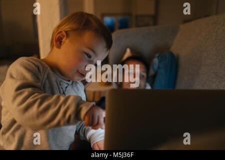 Fille Litle avec les parents à la recherche à l'ordinateur portable sur le canapé dans le noir Banque D'Images